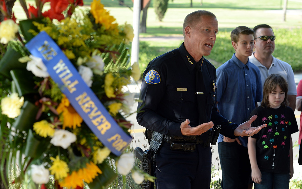 . Friends and police officers pay tribute to Glendora Police Officer Louis Anthony Pompei at his memorial on Puente Street in San Dimas Monday afternoon June 9, 2014. Pompei was killed in the line of duty at a near by market during a robbery attempt in June 1995. (Will Lester/Inland Valley Daily Bulletin)