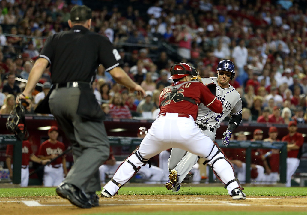 . Troy Tulowitzki #2 of the Colorado Rockies is tagged out at home plate by catcher Miguel Montero #26 of the Arizona Diamondbacks as he attempts to score during the first inning of the MLB game at Chase Field on April 28, 2013 in Phoenix, Arizona.  (Photo by Christian Petersen/Getty Images)