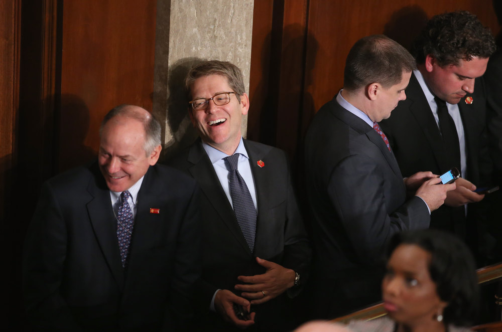 . White House Press Secretary Jay Carney (2nd-R) greets legislators on the floor of the House before U.S. President Barack Obama�s State of the Union address February 12, 2013 in Washington, DC. Facing a divided Congress, Obama is expected to focus his speech on new initiatives designed to stimulate the U.S. economy.  (Photo by Chip Somodevilla/Getty Images)