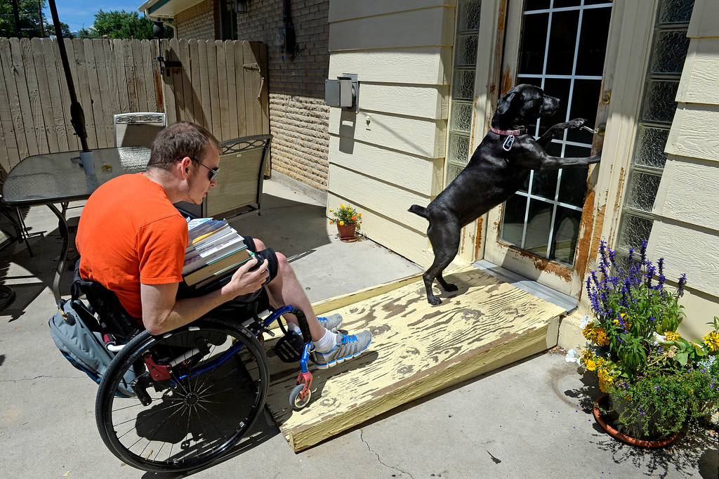 ". LuLu opens a patio door for James, loaded down with school books. She immediately licked his injured legs when he came home from the hospital. ""It was weird, she knew right away... She got me through a lot of this.\"" (Photo By Craig F. Walker / The Denver Post)"