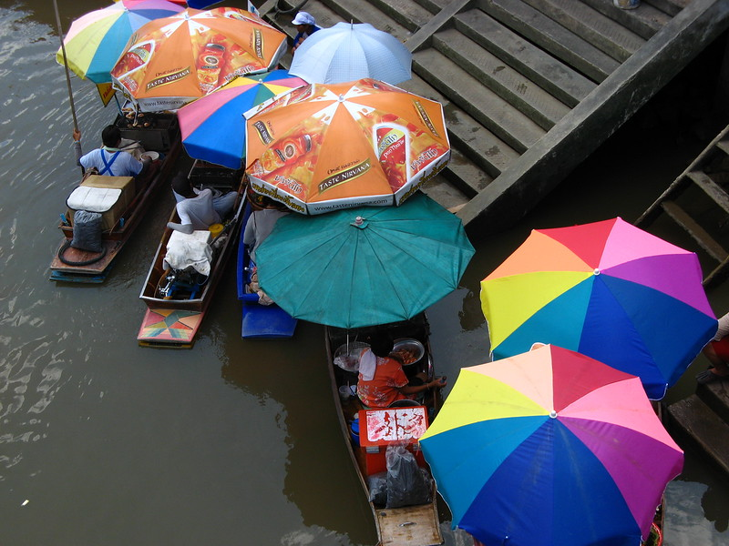 Colorful umbrellas on vendors' boats.
