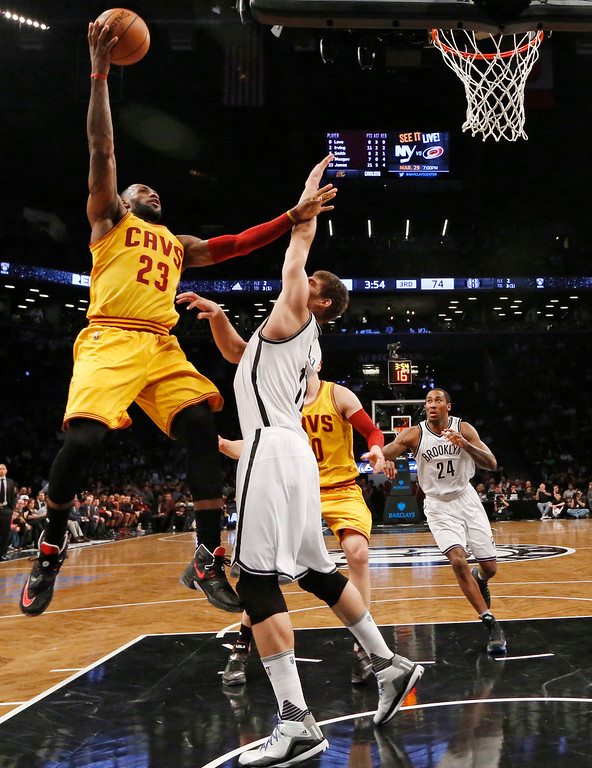 . Cleveland Cavaliers forward LeBron James (23) shoots over Brooklyn Nets center Brook Lopez (11) in the third quarter of an NBA basketball game, Thursday, March 24, 2016, in New York. James had 30. but the Nets beat the Cavaliers 104-95. (AP Photo/Kathy Willens)