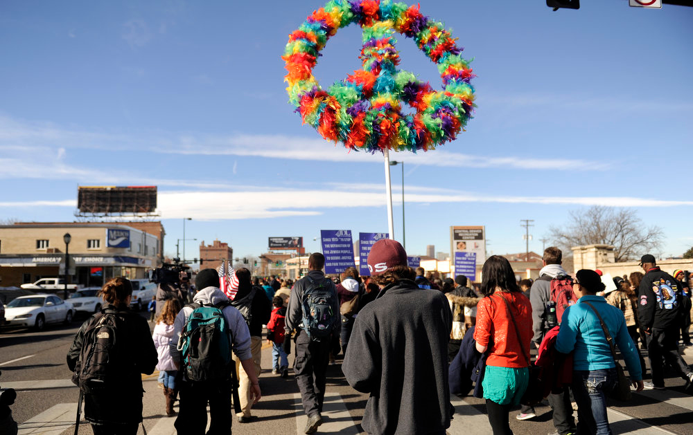 Description of . There were many symbols of peace in  the  Martin Luther King Jr. Marade  as it winds along E. Colfax Ave. on it's way downtown.  The marade, march/parade,  started at the MLK statue in the City Park  on Monday, January 21, 2013.   (Photo By Cyrus McCrimmon / The Denver Post)