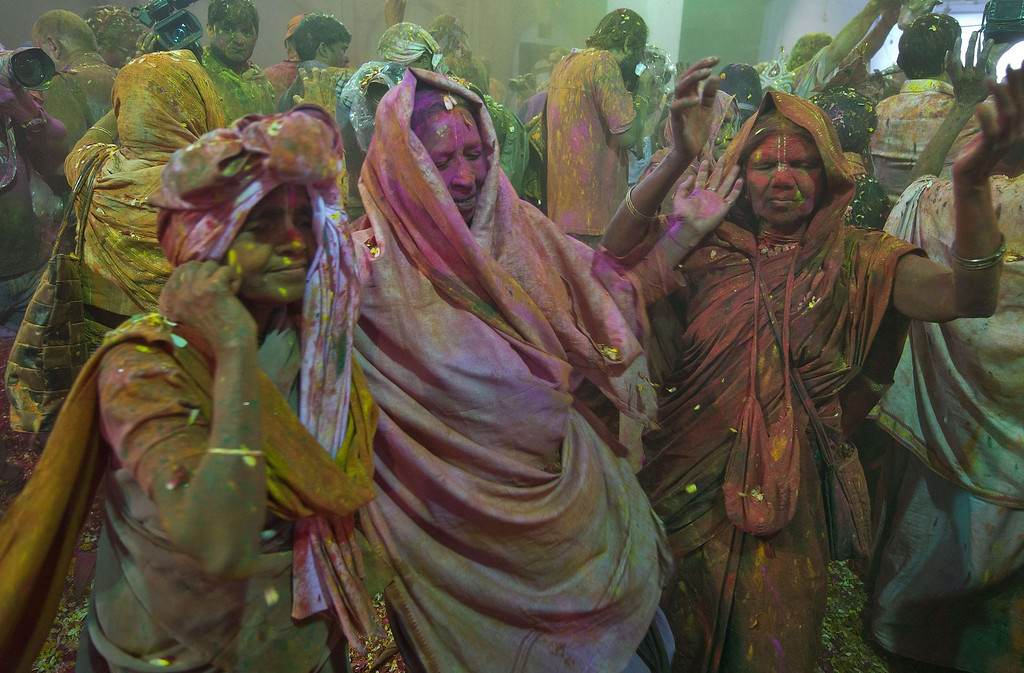 . Indian widows sing and dance while playing Holi with gulal (colored powder), flowers and water  in Vrindavan on March 14, 2014. Breaking centuries-old tradition, around 1,000 widows living in the holy city of Vrindavan celebrated the spring color festival of Holi at Meera Sahabhagini Sadan in Vrindavan. In a symbolic gesture, the widows celebrated Holi with colors and gulal unlike the previous year where they only sprinkled flower petals over each other. As per Indian tradition, widows are considered social outcasts and refrain from celebrating Holi.  AFP PHOTO/Prakash SINGH/AFP/Getty Images