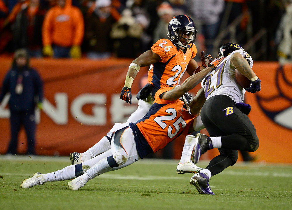 Description of . Baltimore Ravens running back Ray Rice (27) is tackled by Denver Broncos cornerback Chris Harris (25) in the fourth quarter. The Denver Broncos vs Baltimore Ravens AFC Divisional playoff game at Sports Authority Field Saturday January 12, 2013. (Photo by AAron  Ontiveroz,/The Denver Post)