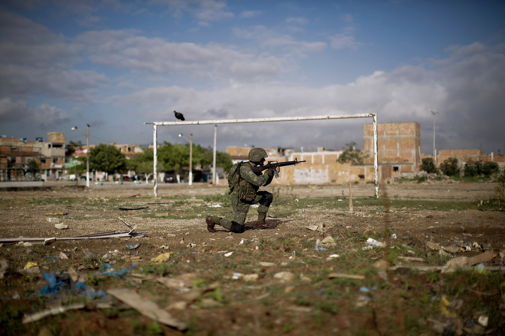 . A navy soldier patrols on a soccer field during an operation to occupy the Mare slum complex in Rio de Janeiro, Brazil, Saturday, April 5, 2014. More than 2,000 Brazilian Army soldiers moved into the Mare slum complex early Saturday in a bid to improve security and drive out the heavily armed drug gangs that have ruled the sprawling slum for decades.(AP Photo/Felipe Dana)