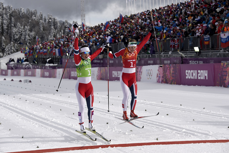 . Gold medalists Norway\'s Marit Bjoergen (L) and Ingvild Flugstad Oestberg celebrate at the finish line in the Women\'s Cross-Country Skiing Team Sprint Classic Final at the Laura Cross-Country Ski and Biathlon Center during the Sochi Winter Olympics on February 19, 2014 in Rosa Khutor near Sochi. (ODD ANDERSEN/AFP/Getty Images)