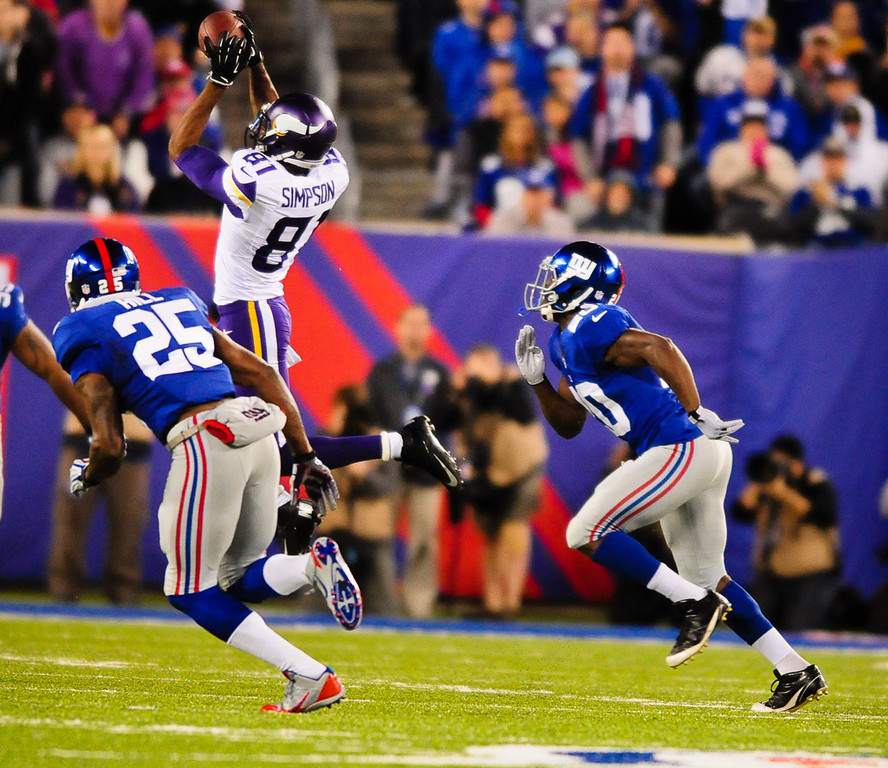 . Vikings wide receiver Jerome Simpson grabs a pass for a first down in the first quarter against the Giants. At left is Giants defensive back Will Hill; cornerback Prince Amukamara is at right.  (Pioneer Press: Ben Garvin)