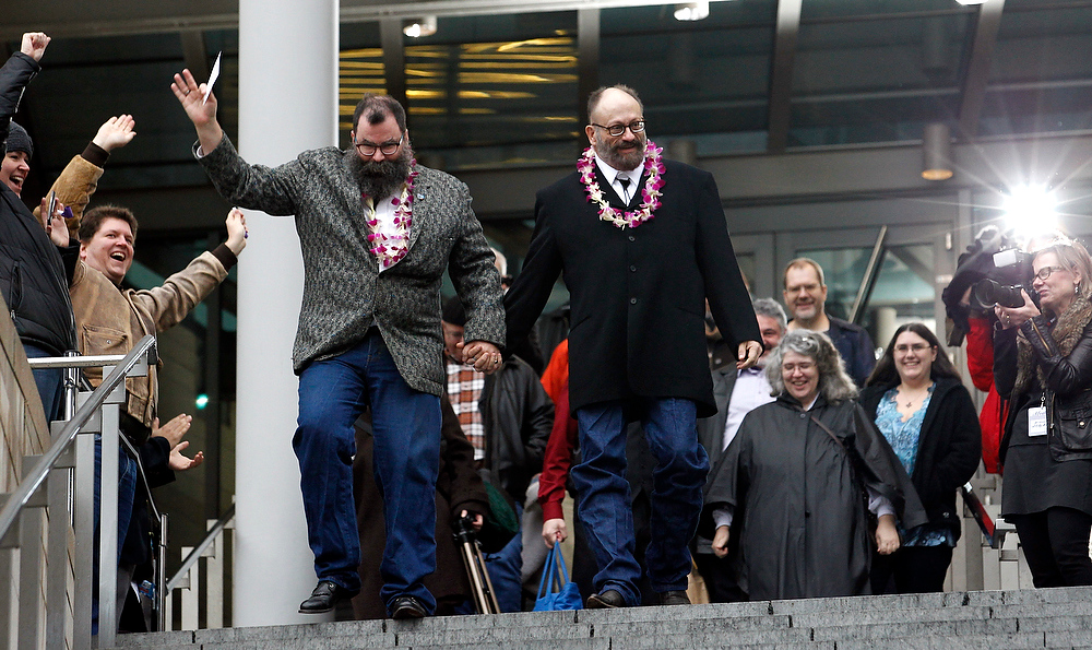 . Liam, right, and Richard Sauer-Wooden are cheered as they depart Seattle City Hall after getting married there, becoming among the first gay couples to legally wed in the state, Sunday, Dec. 9, 2012, in Seattle. Gov. Chris Gregoire signed a voter-approved law legalizing gay marriage Dec. 5 and weddings for gay and lesbian couples began in Washington on Sunday, following the three-day waiting period after marriage licenses were issued earlier in the week. (AP Photo/Elaine Thompson)