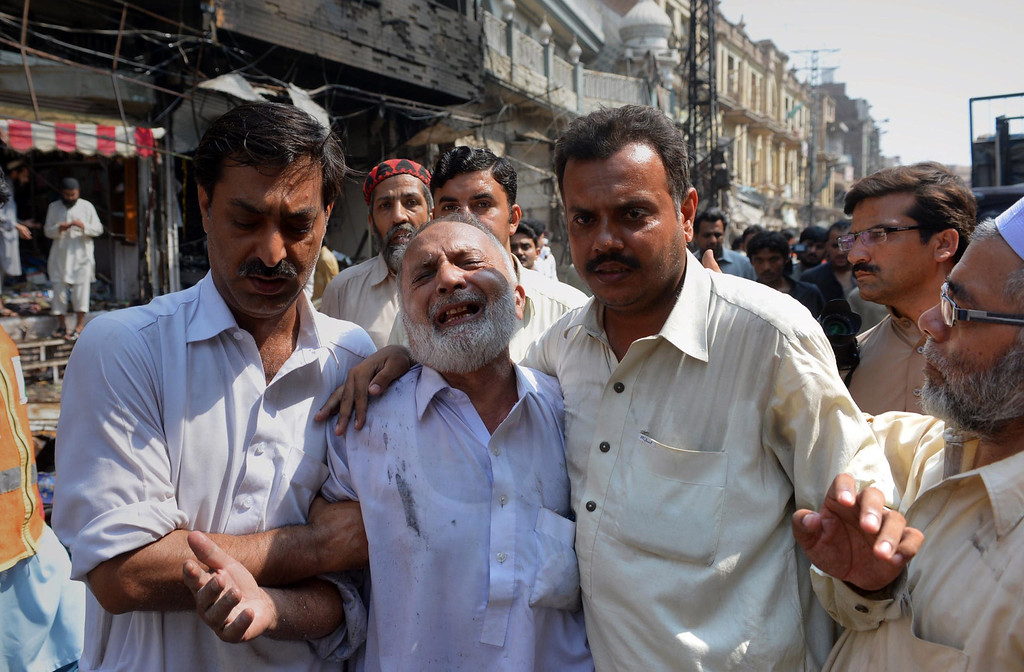 . Pakistani men comfort a mourner at the site of a bomb explosion in the busy Kissa Khwani market in Peshawar on September 29, 2013. AFP PHOTO /  A. MAJEED/AFP/Getty Images