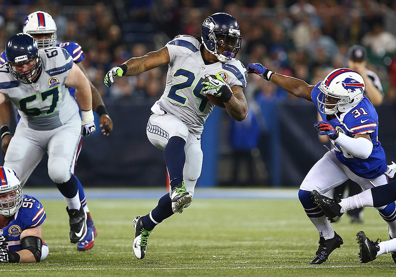. Marshawn Lynch #24 of the Seattle Seahawks carries the ball during an NFL game as Jairus Byrd #31 of the Buffalo Bills attempts to tackle him at Rogers Centre on December 16, 2012 in Toronto, Ontario, Canada. (Photo by Tom Szczerbowski/Getty Images)