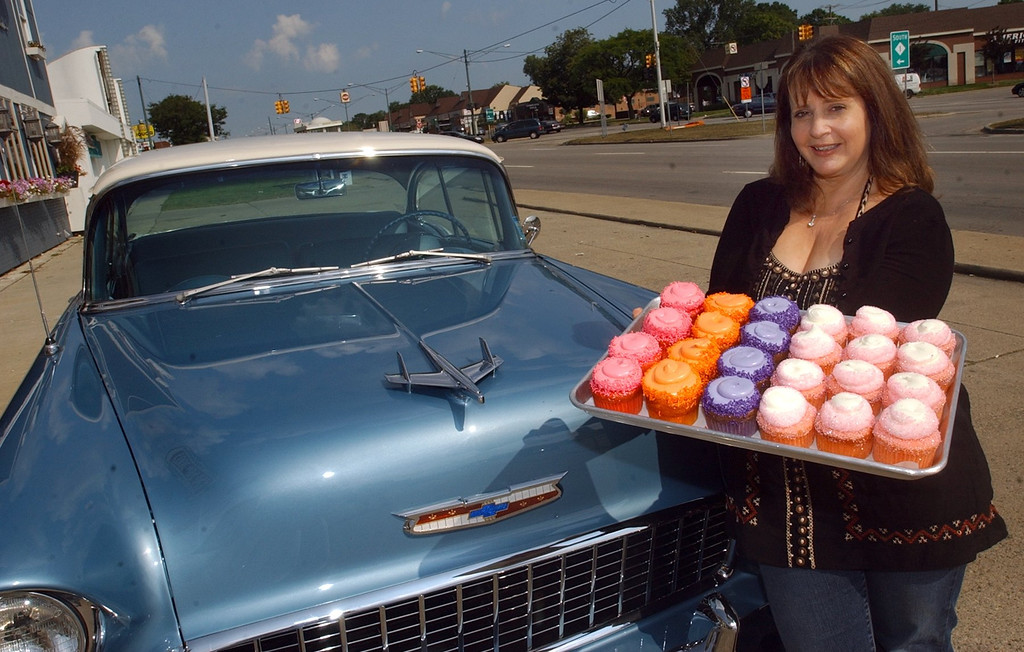 . Pam Turkin, owner of Just Baked cupcakes in Royal Oak, with Faygo red pop, orange pop, grape pop and Pink Cadillac cupcakes for this Saturday\'s Woodward Dream Cruise.