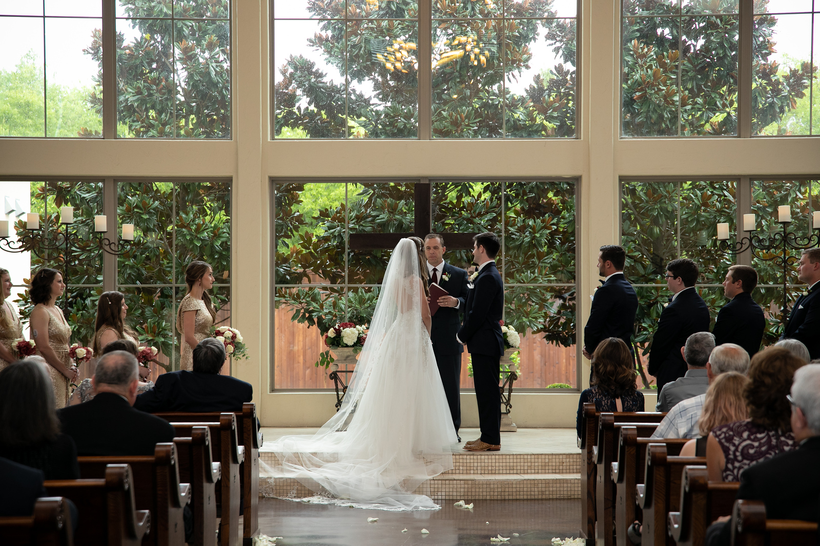 a bride and groom standing at the altar in front of a cross and six huge windows as they wed