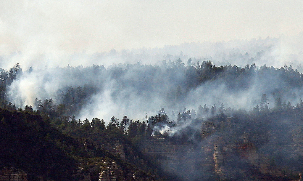 . The Slide Fire burns nearby Oak Creek Canyon on Thursday, May 22, 2014, in Sedona, Ariz.  The fire has burned approximately 4,800 acres. (AP Photo/Ross D. Franklin)