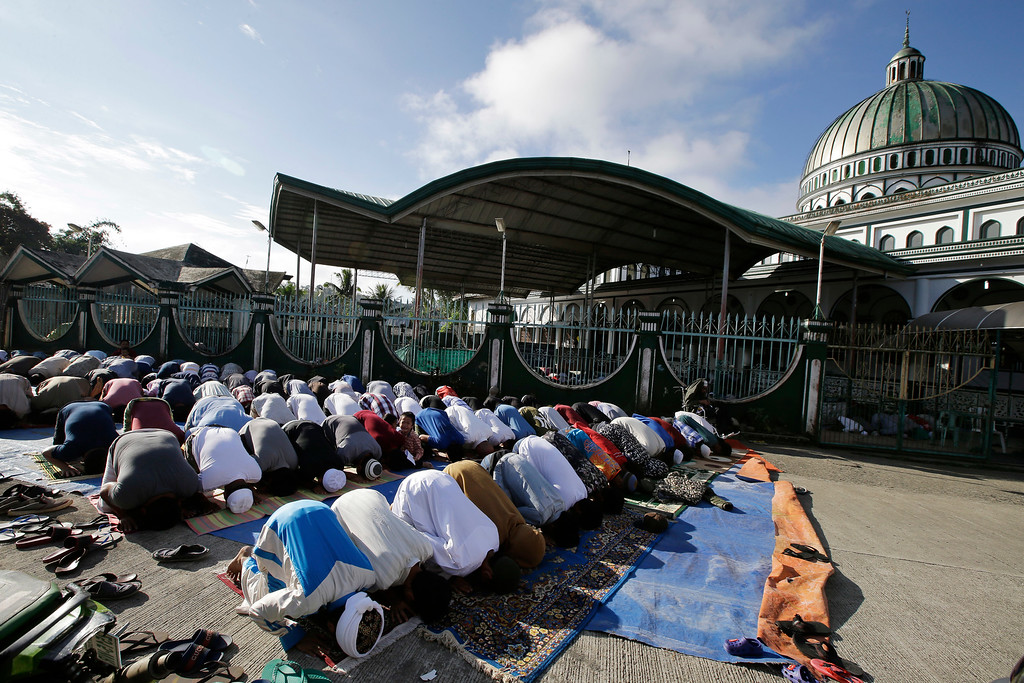 . Survivors offer Eid al-Fitr prayers outside the Saduc Grand Mosque, the biggest mosque that reopened near the former battle area between troops and Islamic extremists, to mark the end of the holy fasting month of Ramadan in Marawi city, southern Philippines, Friday, June 15, 2018. Thousands of displaced residents celebrated Eid al-Fitr inside emergency shelters and the threat of Islamic extremists and unexploded bombs lingers in the rubble after a disastrous five-month siege by Islamic State group-aligned fighters that began more than a year ago. (AP Photo/Aaron Favila)i