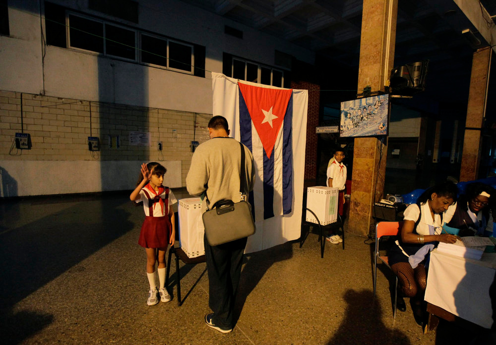 Description of . A school child salutes as a man casts his ballot at a special polling station set up in Havana's main train station February 3, 2013. Cubans go to polls to elect National Assembly representatives. REUTERS/Desmond Boylan