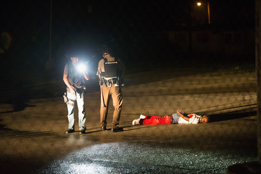 . Police stand over a man with gunshot wounds lying in a parking lot after a shoot out  with police along West Florissant Street during a demonstration to mark the one-year anniversary of the shooting of Michael Brown on August 9, 2015 in Ferguson, Missouri. The shooter is listed  in critical condition in an area hospital.  Michael Brown\'s death sparked months of sometimes violent protests in Ferguson and drew nationwide focus on police treatment of black suspects.  (Photo by Scott Olson/Getty Images)