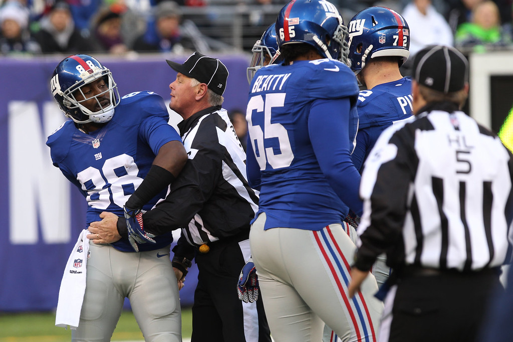 . New York Giants wide receiver Hakeem Nicks (88) is restrained by back judge Keith Ferguson during a scuffle between Giants and Seattle Seahawks players on an interception by Seahawks\' Richard Sherman at the end of the first half an NFL football game on Sunday, Dec. 15, 2013, in East Rutherford, N.J. (AP Photo/Peter Morgan)