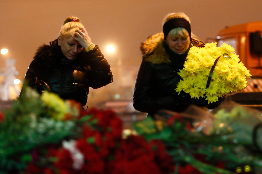 . Women cry while laying flowers outside the Volgograd main railway station in Volgograd, Russia, early Monday Dec. 30, 2013. Russian authorities ordered police to beef up security at train stations and other facilities across the country after a suicide bomber killed 14 people on a bus Monday in the southern city of Volgograd. It was the second deadly attack in two days on the city that lies just 400 miles (650 kilometers) from the site of the 2014 Winter Olympics. (AP Photo/Denis Tyrin)