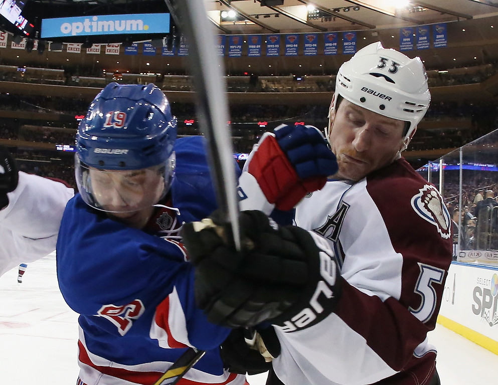 . NEW YORK, NY - NOVEMBER 13: Jesper Fast #19 of the New York Rangers and Cody McLeod #55 of the Colorado Avalanche collide on the boards at Madison Square Garden on November 13, 2014 in New York City. The Avalanche defeated the Rangers 4-3 in the shootout. (Photo by Bruce Bennett/Getty Images)
