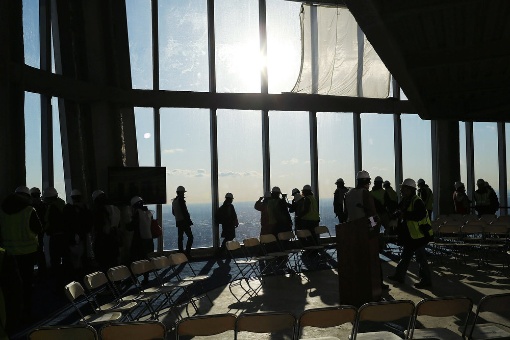 . Visitors stand near the windows of the One World Observatory from the 100th floor of One World Trade Center at the Ground Zero site on April 2, 2013 in New York City. One World Observatory, which is situated more than 1,250 feet over lower Manhattan, will open to the public in 2015 and will include a pre-show theater, multiple spaces that allow for panoramas of the New York City region and numerous dining options. When completed, One World Trade Center will be the tallest building in the Western Hemisphere at 1776 feet.  (Photo by Spencer Platt/Getty Images)