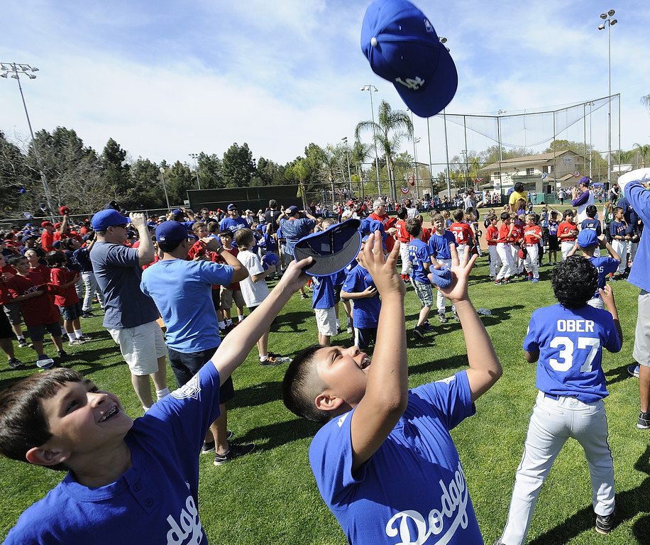 . LONG BEACH, CALIF. USA -- Anthony Muro, center, and William Rodriguez celebrate after the National Anthem during opening ceremonies for The Los Altos Youth Baseball and Softball league at El Dorado Park in Long Beach, Calif. on March 2, 2013.  Photo by Jeff Gritchen / Los Angeles Newspaper Group