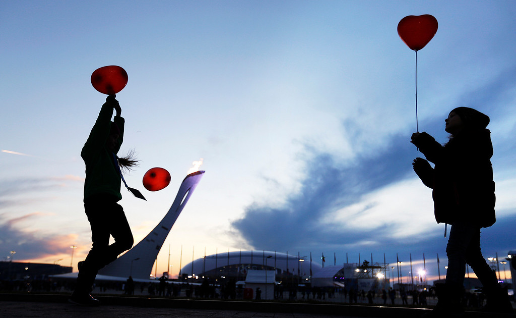 . The Olympic flame burns in the background at the Olympic Park as children play with heart shaped balloons in celebration of Valentine\'s Day at the 2014 Winter Olympics, Friday, Feb. 14, 2014, in Sochi, Russia. (AP Photo/David Goldman)