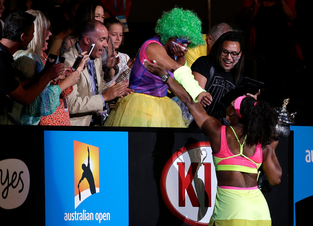 . Serena Williams of the U.S. celebrates with a fan,  as she paraded on Rod Laver Arena, after defeating Maria Sharapova of Russia in the women\'s singles final at the Australian Open tennis championship in Melbourne, Australia, Saturday, Jan. 31, 2015. (AP Photo/Vincent Thian)