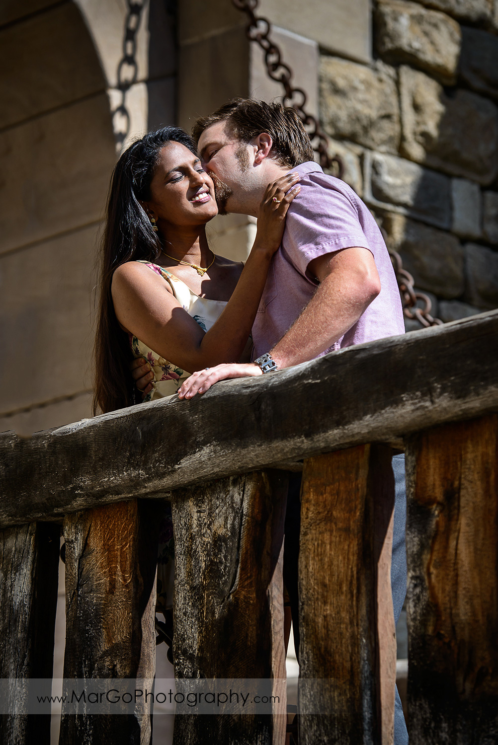 man in pink shirt kissing Indian woman in flower dress in front of the castle main gate during engagement session at Castello di Amorosa in Calistoga