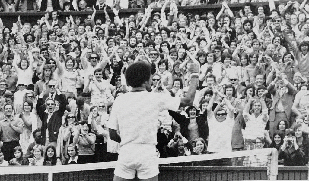 . Tennis star Arthur Ashe, the new men\'s singles champion of the All-England Lawn Tennis Championship of Richmond, Va., gives the clenched fist salute to a delighted crowd at Wimbledon after his 6-1, 6-1, 5-7, 6-4 victory over the former titleholder Jimmy Connors of Belleville, Ill., July 5, 1975.  (AP Photo/RJP)