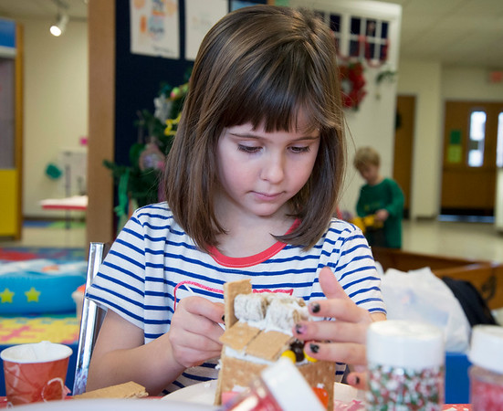 12/27/19 Wesley Bunnell | StaffrrGingerbread house making took place on Friday afternoon at the New Britain Youth Museum in New Britain. Maeve McCarthy, age 6, works her house with plenty of goodies to choose from.