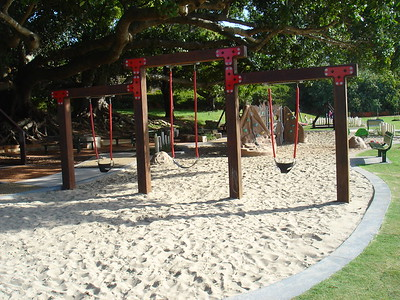 triple timber swing in sandpit with concrete edging