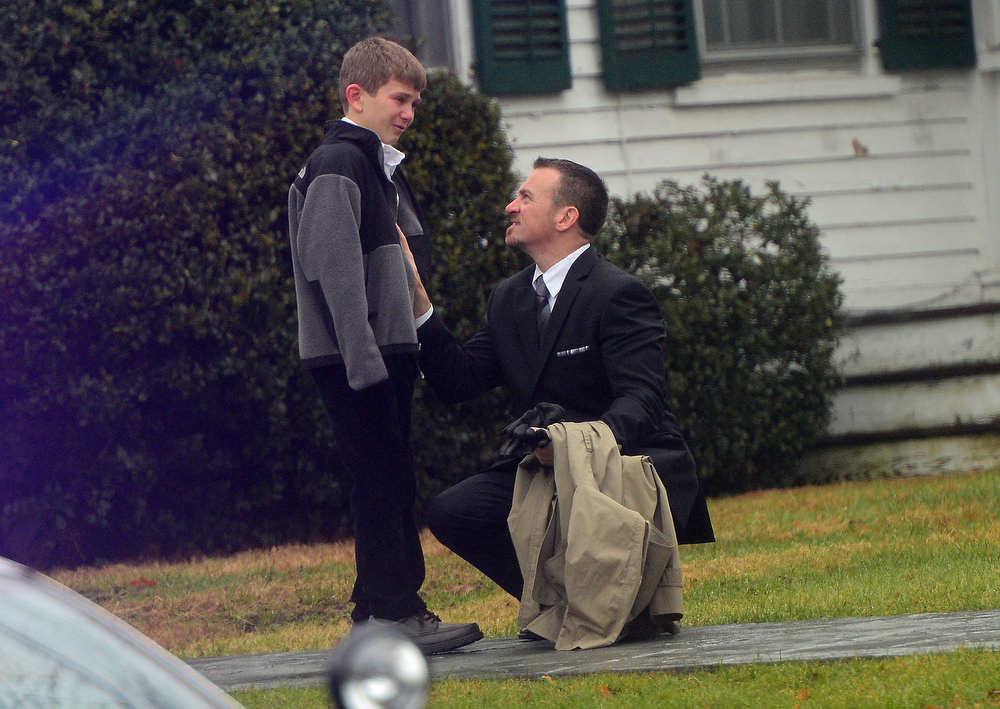 Description of . A man comfort a young mourner at Honan funeral while attending the funeral for Jack Pinto, 6, one of the victims of the Sandy Hook elementary school shooting, on December 17, 2012, in Newtown, Connecticut. Funerals began in the little Connecticut town of Newtown after the school massacre that took the lives of 20 small children and six staff, triggering new momentum for a change to America's gun culture. AFP PHOTO/Emmanuel DUNAND/AFP/Getty Images