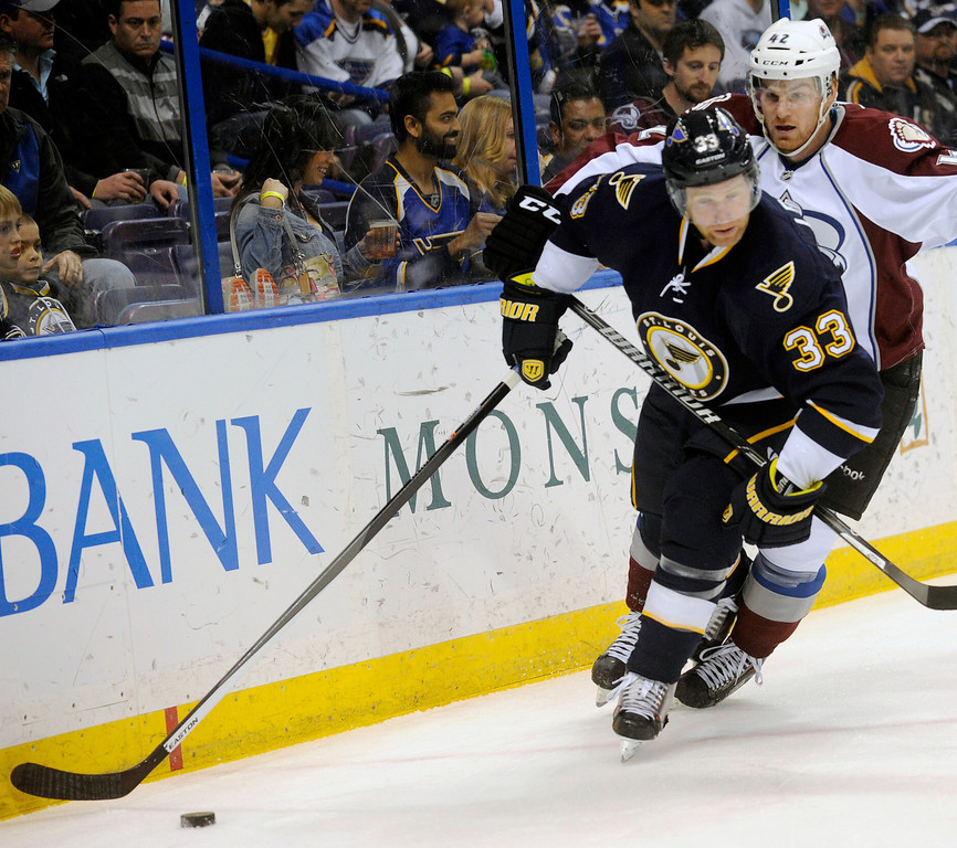 . St. Louis Blues\' Jordan Leopold (33) skates around Colorado Avalanche\'s Brad Malone during the first period of an NHL hockey game, Saturday, April 5, 2014, in St. Louis. (AP Photo/Bill Boyce)