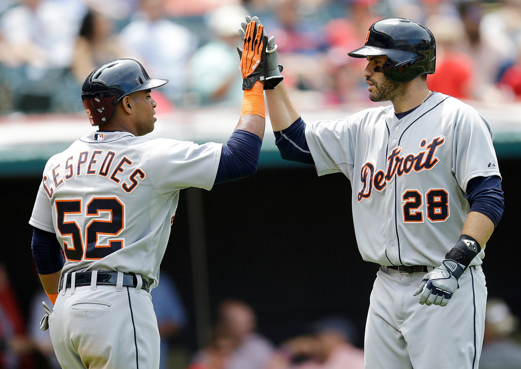 . Detroit Tigers\' Yoenis Cespedes (52) congratulates J.D. Martinez (28) after Martinez hit a two-run home run off Cleveland Indians starting pitcher Carlos Carrasco in the seventh inning of a baseball game, Wednesday, June 24, 2015, in Cleveland. Cespedes scored on the play. (AP Photo/Tony Dejak)