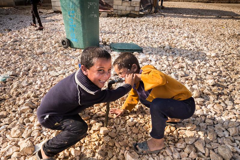 Children playing with water in a refugee camp at the Syrian border in Lebanon. Bekaa Valley, Lebanon. November 2015. ----------- Des enfants jouent avec de l'eau dans un camp de réfugiés à la frontière syrienne au Liban. Vallée de la Bekaa, Liban. Novembre 2015.