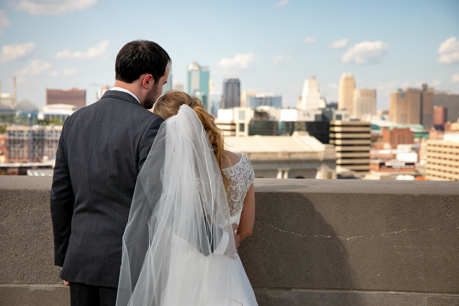 bride and groom look out to the kansas city skyline on a rooftop on the afternoon before their wedding