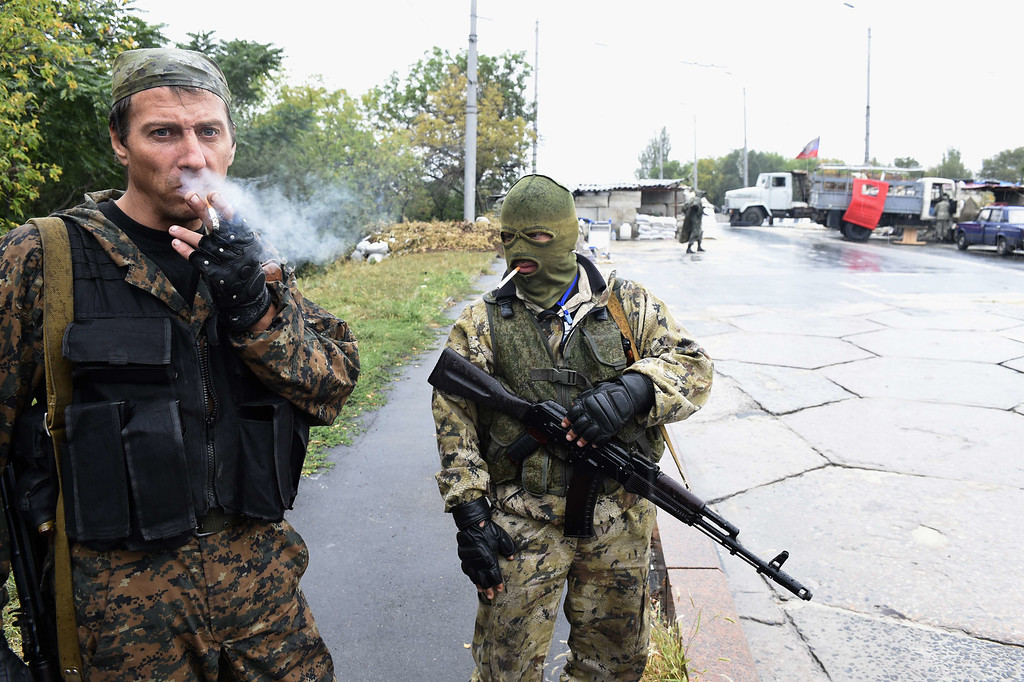 . Pro-Russian separatist fighters smoke as they stand guard at a checkpoint on September 10, 2014 on a road of the Donetsk airport.   Ukrainian President Petro Poroshenko said on Wednesday that most Russian troops had been withdrawn from the country, in a move he said boosted the prospects for peace.  AFP PHOTO/PHILIPPE DESMAZESPHILIPPE DESMAZES/AFP/Getty Images
