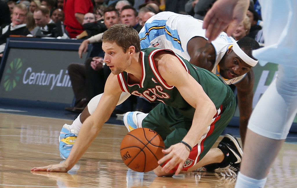 . Milwaukee Bucks guard Luke Ridnour, front, picks up loose ball as Denver Nuggets guard Ty Lawson covers in the first quarter of an NBA basketball game in Denver, Wednesday, Feb. 5, 2014. (AP Photo/David Zalubowski)