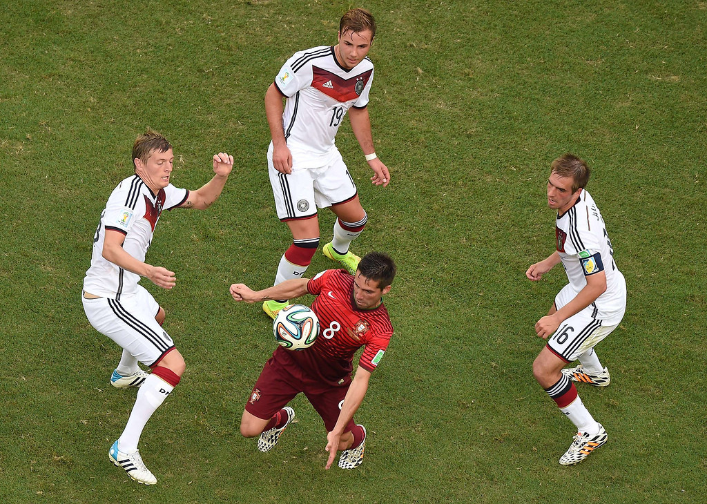 . Portugal\'s midfielder Joao Moutinho (C) controls the ball as Germany\'s defender and captain Philipp Lahm (R) Germany\'s forward Mario Goetze (TOP) and Germany\'s defender Per Mertesacker (L) look on during the Group G football match between Germany and Portugal at the Fonte Nova Arena in Salvador on June 16, 2014, during the 2014 FIFA World Cup.      AFP PHOTO/POOL FRANCOIS XAVIER MARIT/AFP/Getty Images