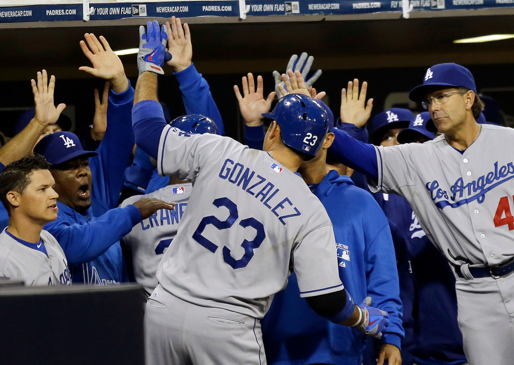 . Los Angeles Dodgers\' Adrian Gonzalez high-fives his way into the dugout after his home run against the San Diego Padres during the first inning of a baseball game in San Diego, Thursday, April 11, 2013. (AP Photo/Lenny Ignelzi)