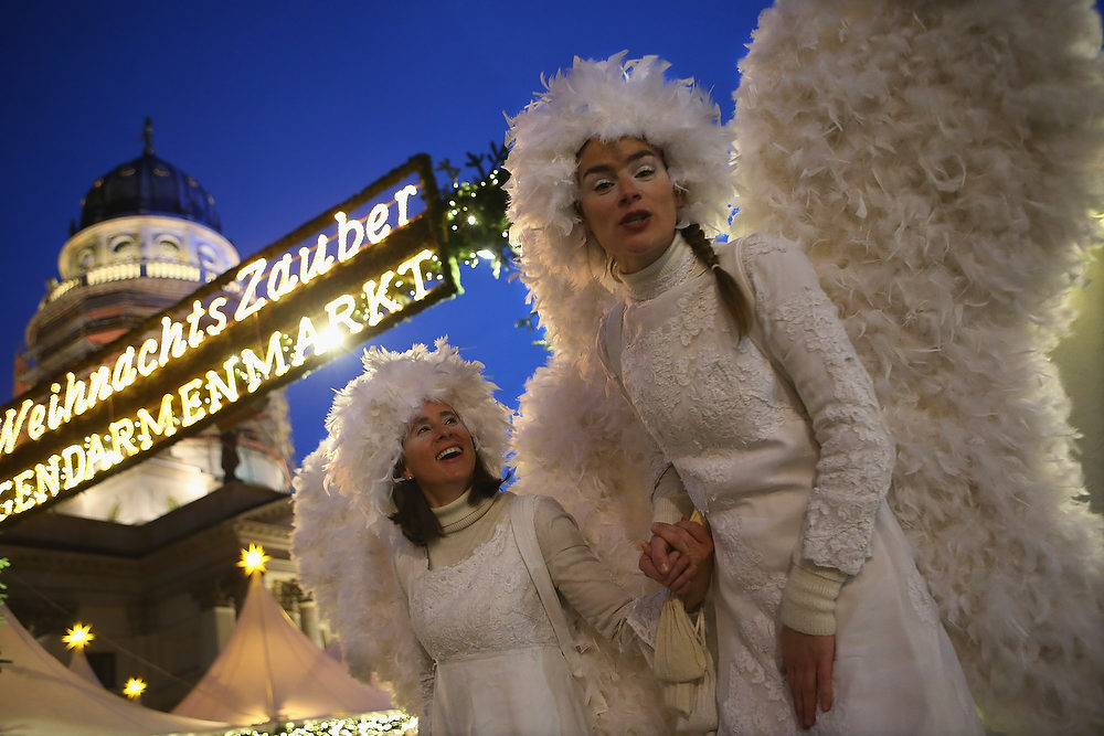 Description of . Hostesses on stilts and dressed as angels walk through the annual Christmas market at Gendarmenmarkt on its opening day on November 26, 2012 in Berlin, Germany. Christmas markets, with their stalls selling mulled wine, Christmas tree decorations and other delights, are an integral part of German Christmas tradition, and many of them opened across Germany today.  (Photo by Sean Gallup/Getty Images)