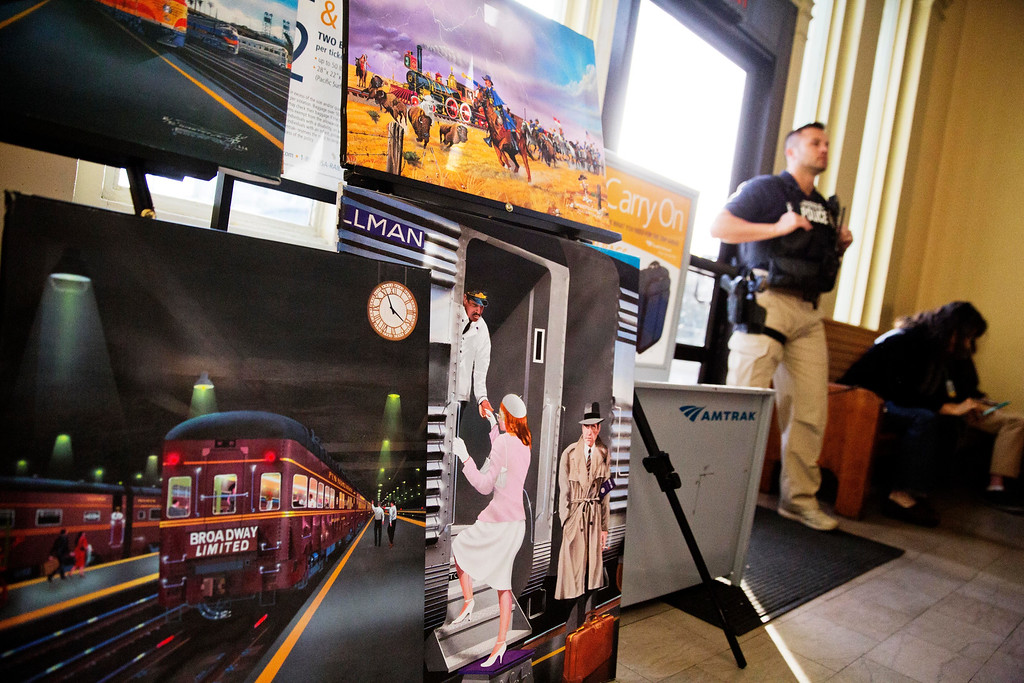 . Artwork by railroad illustrator Robert West is displayed in a waiting room as a Department of Homeland Security official stands in an Amtrak train station in Atlanta, Wednesday, Nov. 23, 2016. Almost 49 million people are expected to travel 50 miles or more for the Thanksgiving holiday, the most since 2007, according to AAA. (AP Photo/David Goldman)