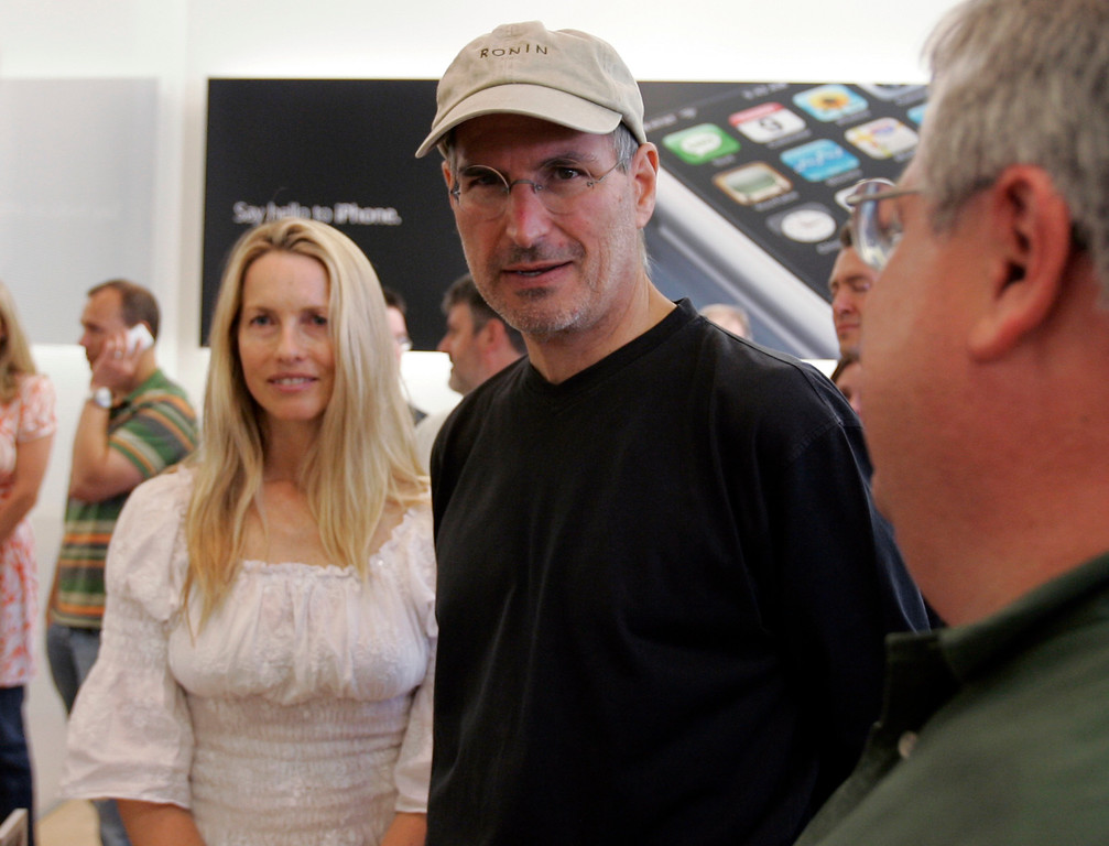 . Apple CEO Steve Jobs, center, and his wife Laurene Powell  meet with customers after the launch of the new Apple iPhone in Palo Alto, Calif., Friday, June 29, 2007. (AP Photo/Paul Sakuma)