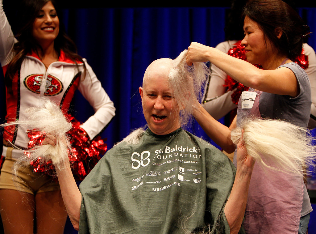 . Pia Chamberlain holds her hair as she has her head shaved by volunteer Stephanie Tran for the St. Baldrick\'s Day head shaving event in support of research for pediatric cancer sponsored by the St. Baldrick\'s Foundation in the NetApp gymnasium at NetApp in Sunnyvale, Calif., on Thursday, March 14, 2013.  (Nhat V. Meyer/Staff)