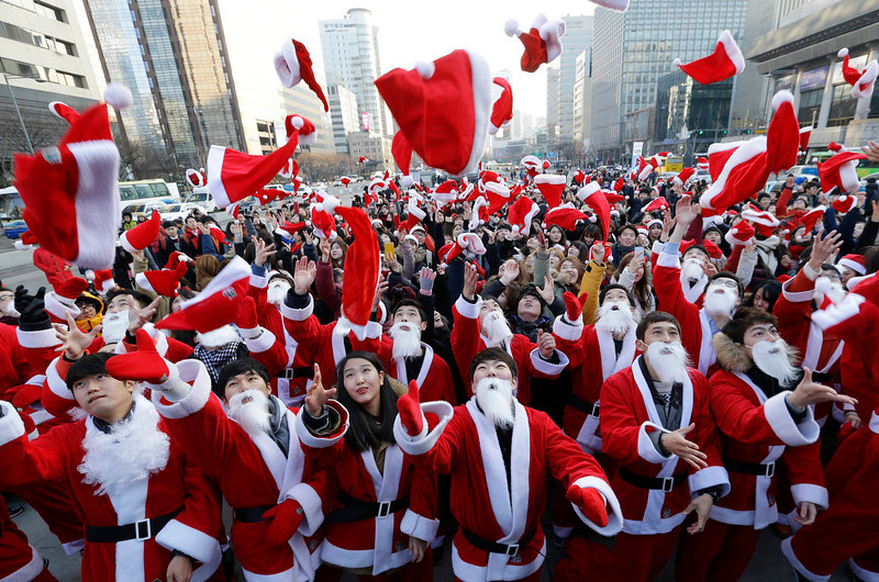 . Volunteers clad in Santa Claus costumes throw their hats in the air as they gather to deliver gifts for the poor in downtown Seoul, South Korea, Wednesday, Dec. 24, 2014. (AP Photo/Ahn Young-joon)