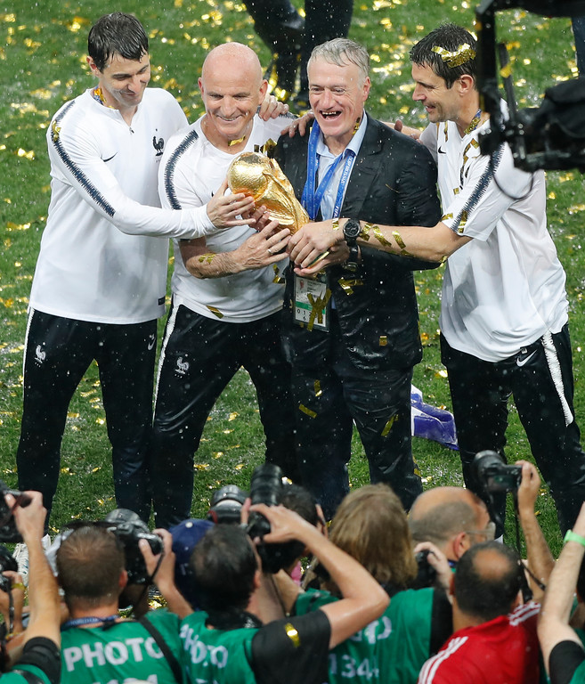 . France head coach Didier Deschamps, second right, holds the trophy at the end of the final match between France and Croatia at the 2018 soccer World Cup in the Luzhniki Stadium in Moscow, Russia, Sunday, July 15, 2018. (AP Photo/Frank Augstein)