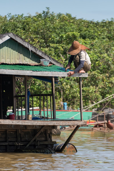 Man repairing roof of his stilt house on Tonle Sap Lake, Kampong Phluk, Siem Reap, Cambodia