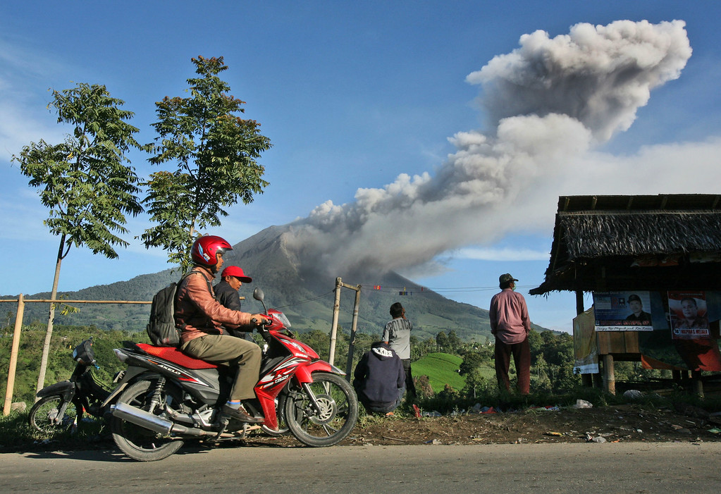 . Villagers watch Mount Sinabung spewing volcanic ash into in Tiga Pancur, North Sumatra, Indonesia, Monday, Nov. 25, 2013. Powerful bursts of hot ash and gravel erupted from the rumbling volcano in western Indonesia Monday, a day after authorities had raised the volcano\'s alert status to the highest level. (AP Photo/Binsar Bakkara)