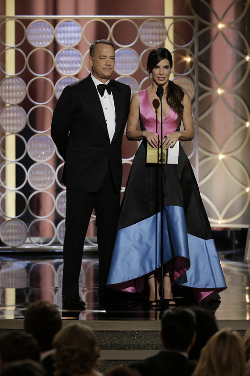 . In this handout photo provided by NBCUniversal, Presenters Tom Hanks and Sandra Bullock speak onstage during the 71st Annual Golden Globe Award at The Beverly Hilton Hotel on January 12, 2014 in Beverly Hills, California.  (Photo by Paul Drinkwater/NBCUniversal via Getty Image)